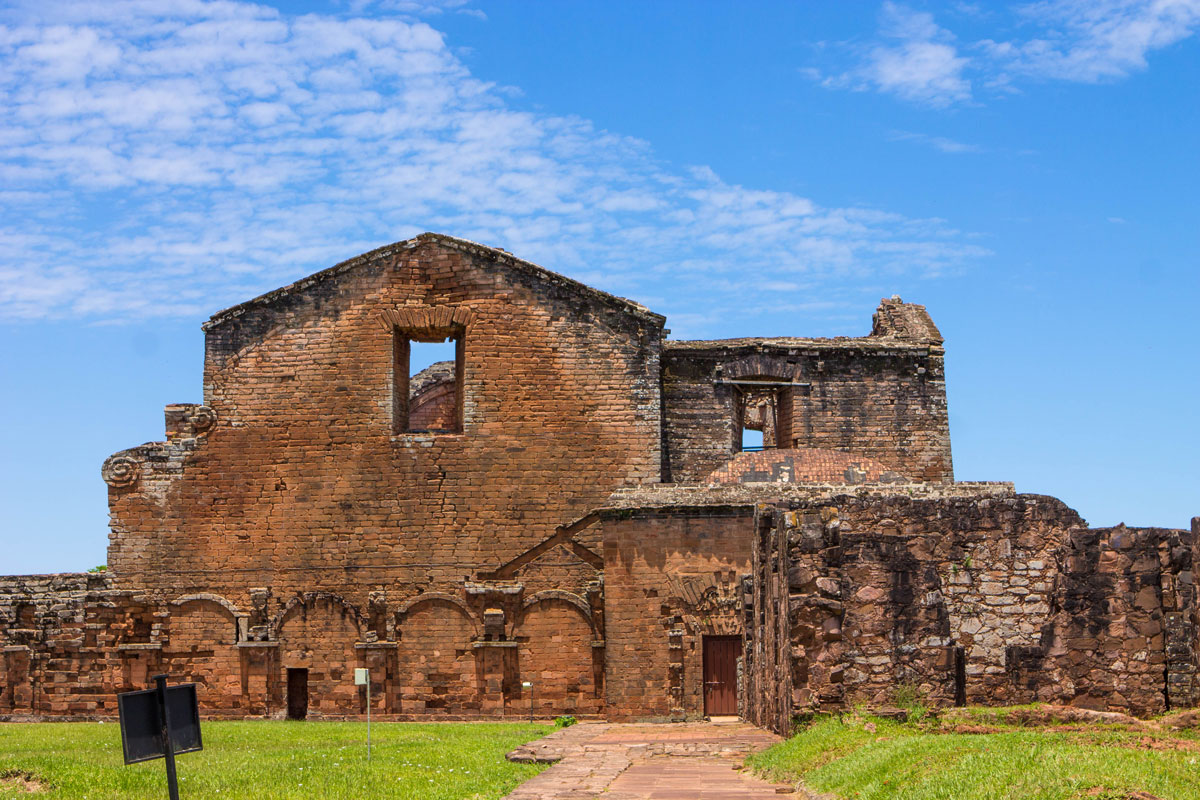 Broken stone and roof peaks marked by large window in the ruins of Trinidad in Paraguay