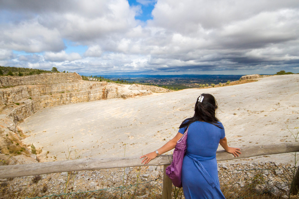 A young womanan looks over a quarry in Portugal that is filled with dinosaur footprints
