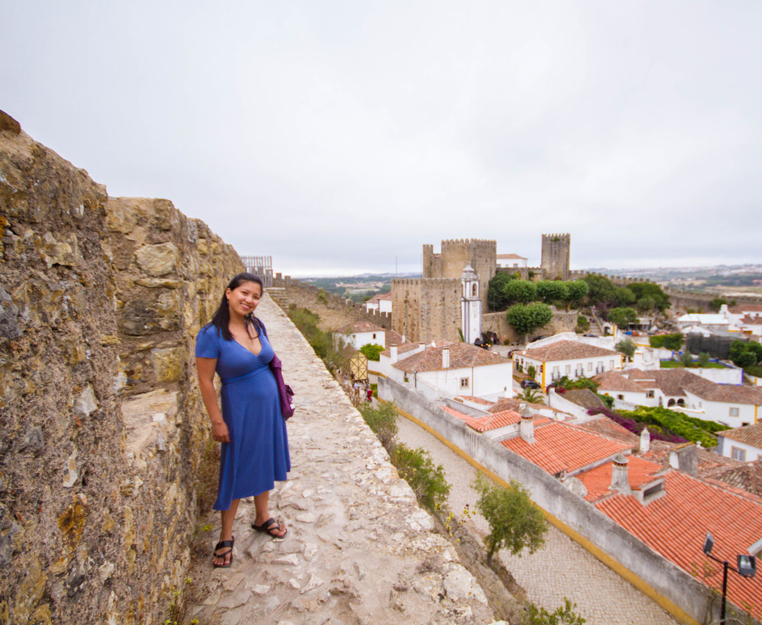 A woman in a blue dress stands on the inside walls of the city of Obidos, Portugal while the castle stands in the background
