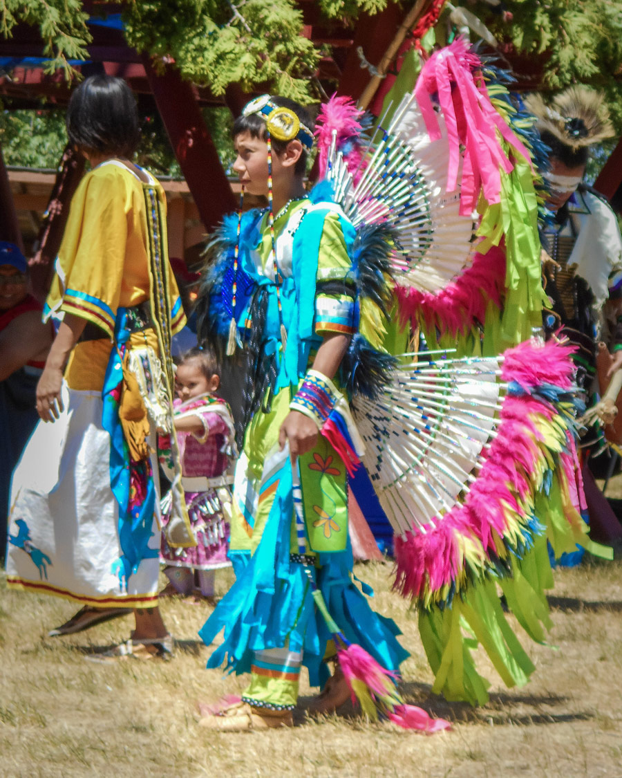 An adolescent dancer in colorful regalia at a First Nations Pow Wow