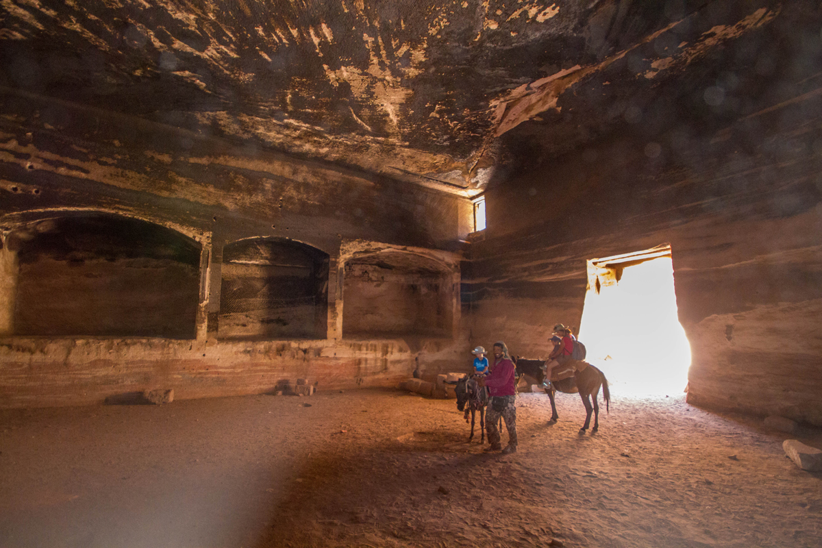 Petra with kids A Bedouin guides a woman and two boys on horseback through the tomb of the roman soldier in Petra Jordan