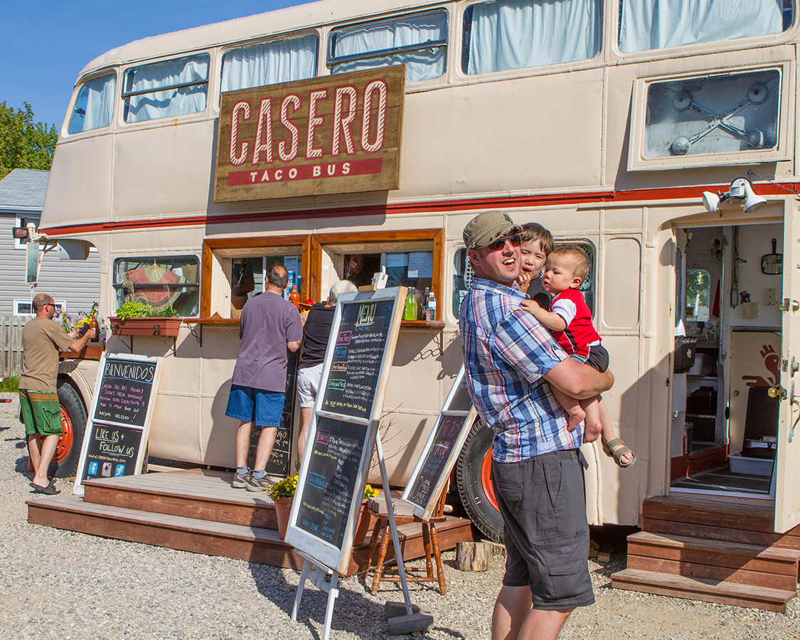 Man and boys waiting at Casero Taco Bar in Sauble Beach town.
