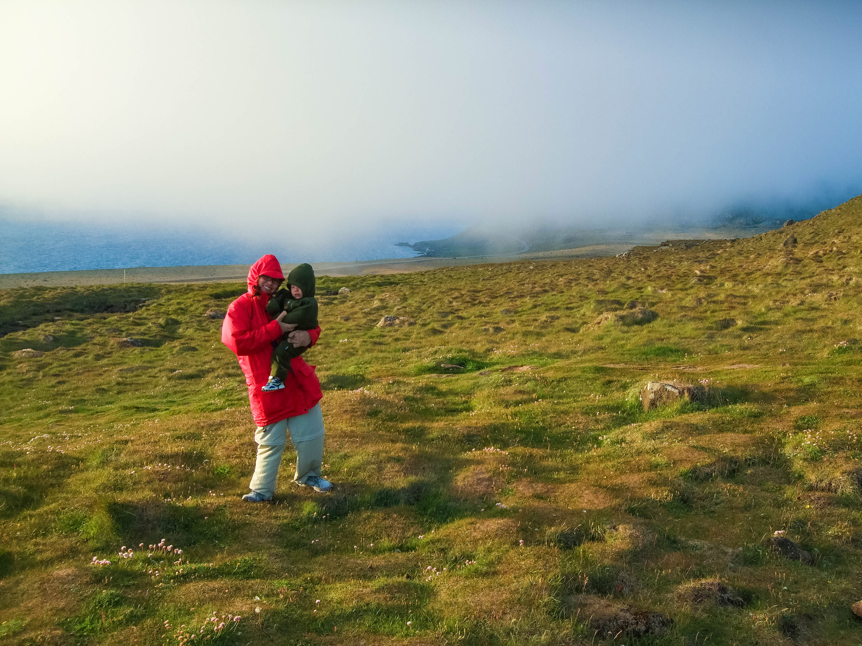 A mother and son brace against the wind as they experience one of the family friendly hikes in Iceland along the Latrabjarg Bird Cliffs in Icelands Westfjords