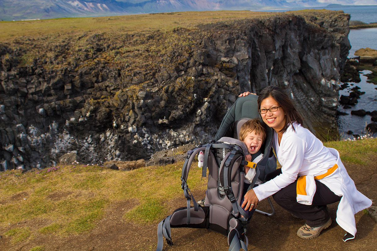 A mother smiles kneeling next to a young boy in a kid-carrier on a hike in Arnarpstapi Iceland