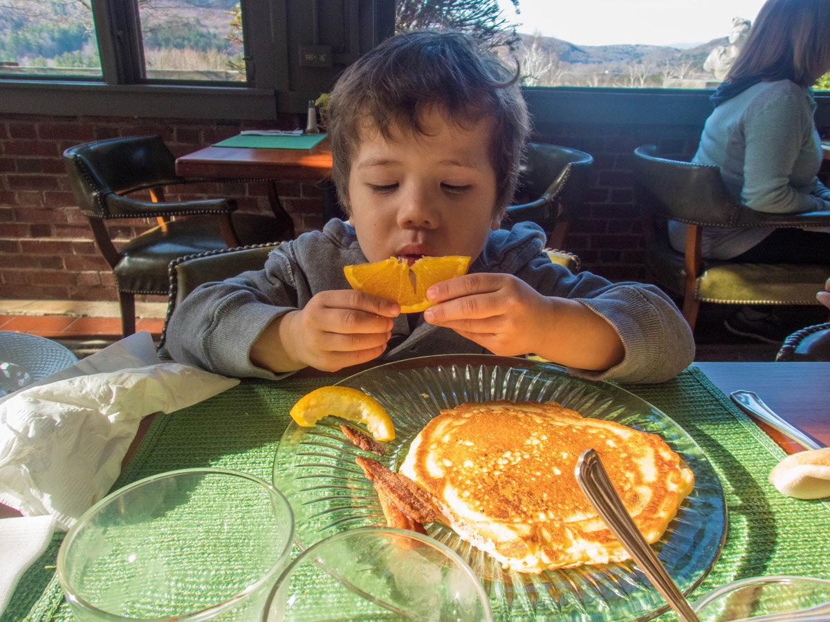 Boy enjoying the fresh fruit at breakfast at the Wilburton Inn in Manchester, Vermont.