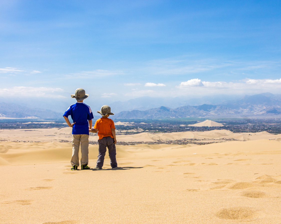 Two young boys hold hands while looking out over the town of Ica from the desert near Huacachina as the go sandboarding with kids in Peru