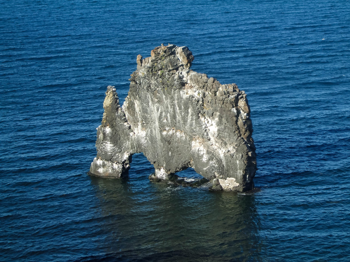 The arched stone monolith Hvammstang off the coast of the Vatnsnes Peninsula in Iceland