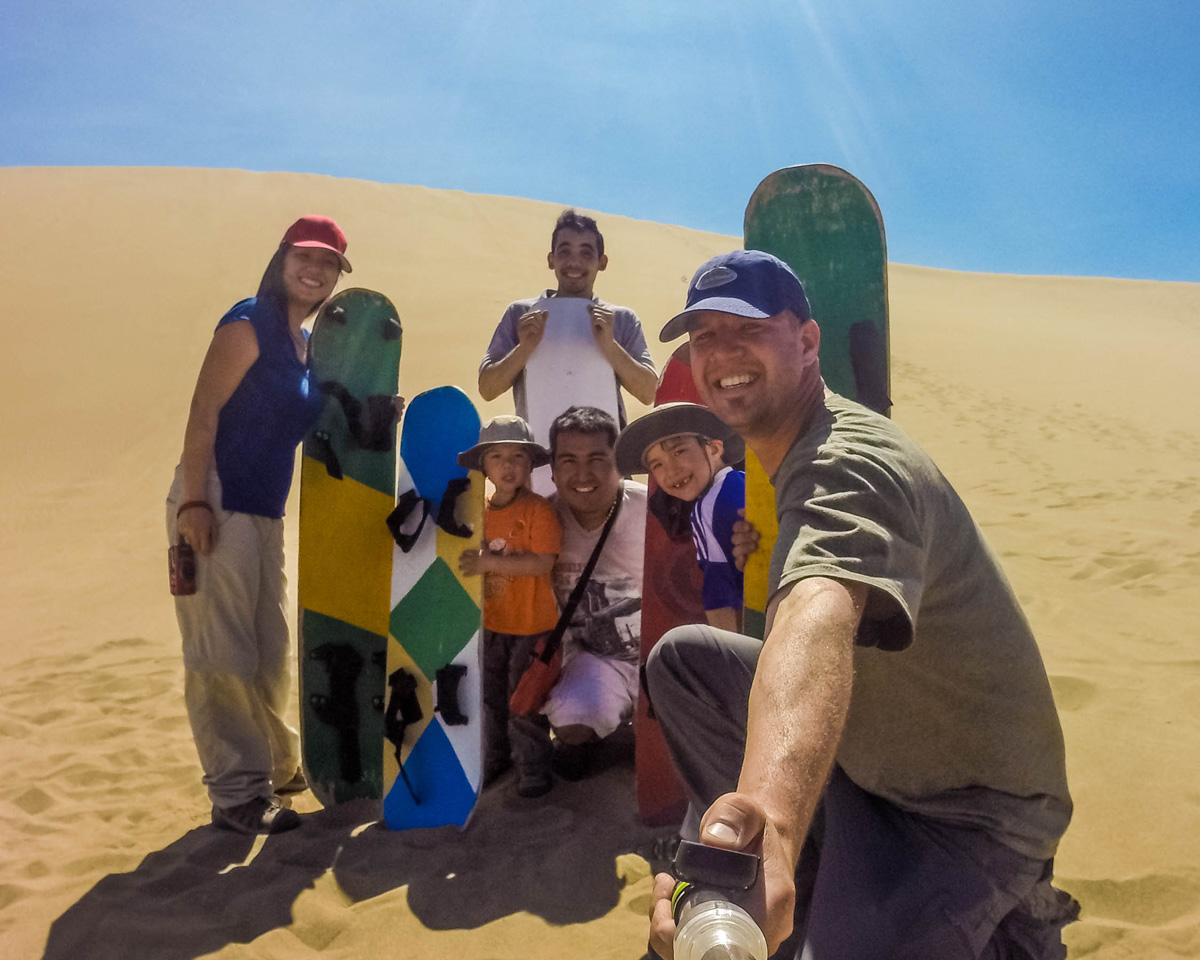 a group shot of sandboarders in Huacachina, Peru