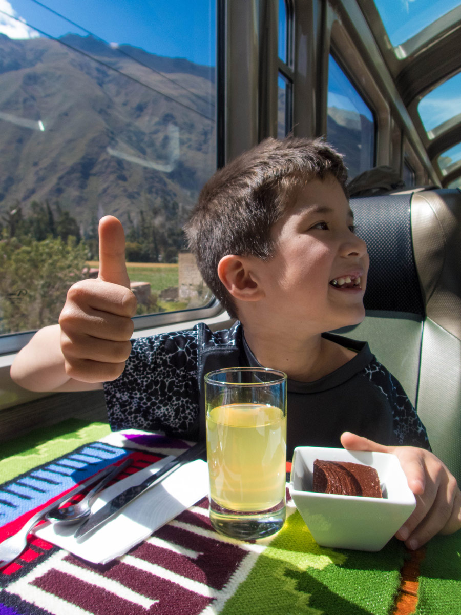 Machu Picchu with kids - Boy enjoying the chocolate cake dessert on the Vistadome train on the way to Macchu Picchu.