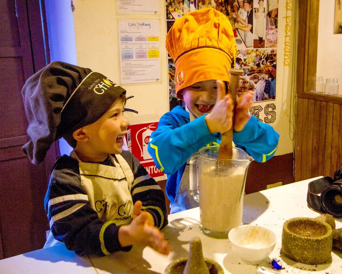 Two young boys stir a jug of homemade hot chocolate at the Cusco ChocoMuseo in Peru