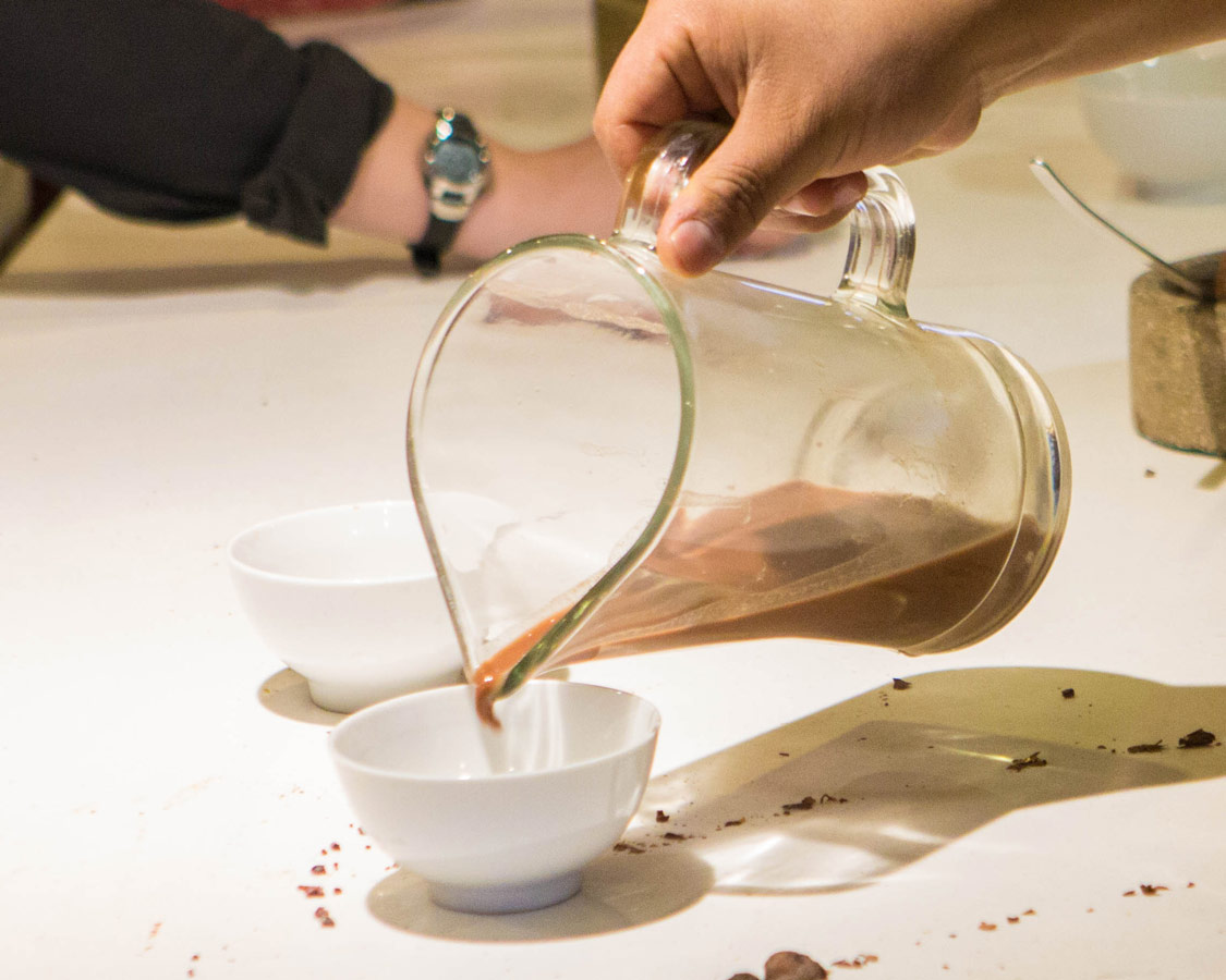 A hand pours chocolate tea into a bowl at the ChocoMuseo in Cusco Peru