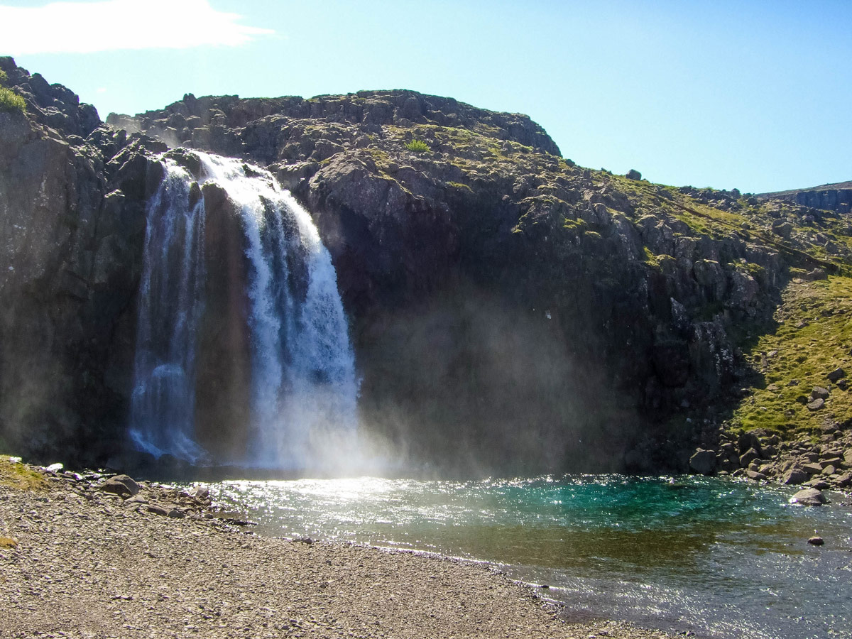 A small waterfall pours over a cliff along the highway in Iceland's westfjords
