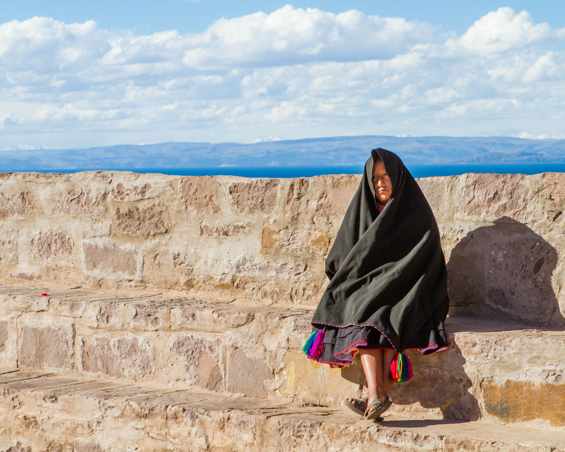 A Taquilenos woman in traditional clothing sits on a stone wall on Taquile island on Lake Titicaca Peru