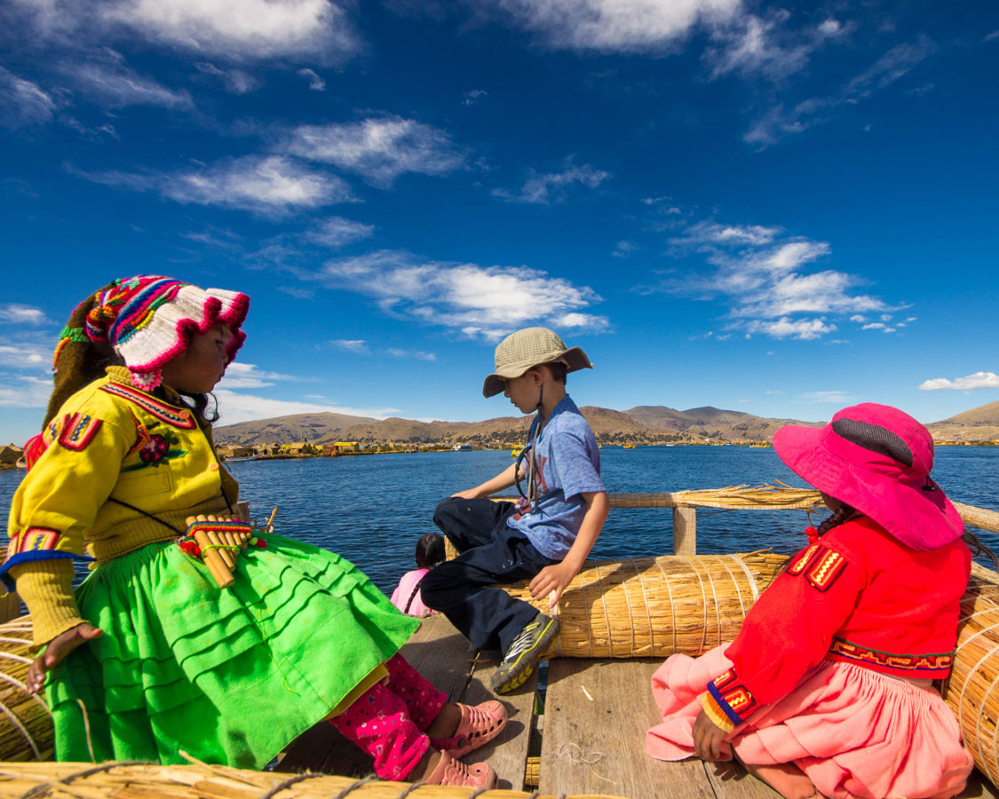 A young traveler sits with local Uru children in colorful traditional clothing on the roof of a balsa boat while his family explores Lake Titicaca with Kids