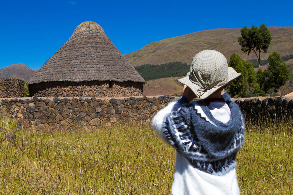 A young boy takes a photograph of the Raqchi Inca ruins on his way to visiting Lake Titicaca with kids