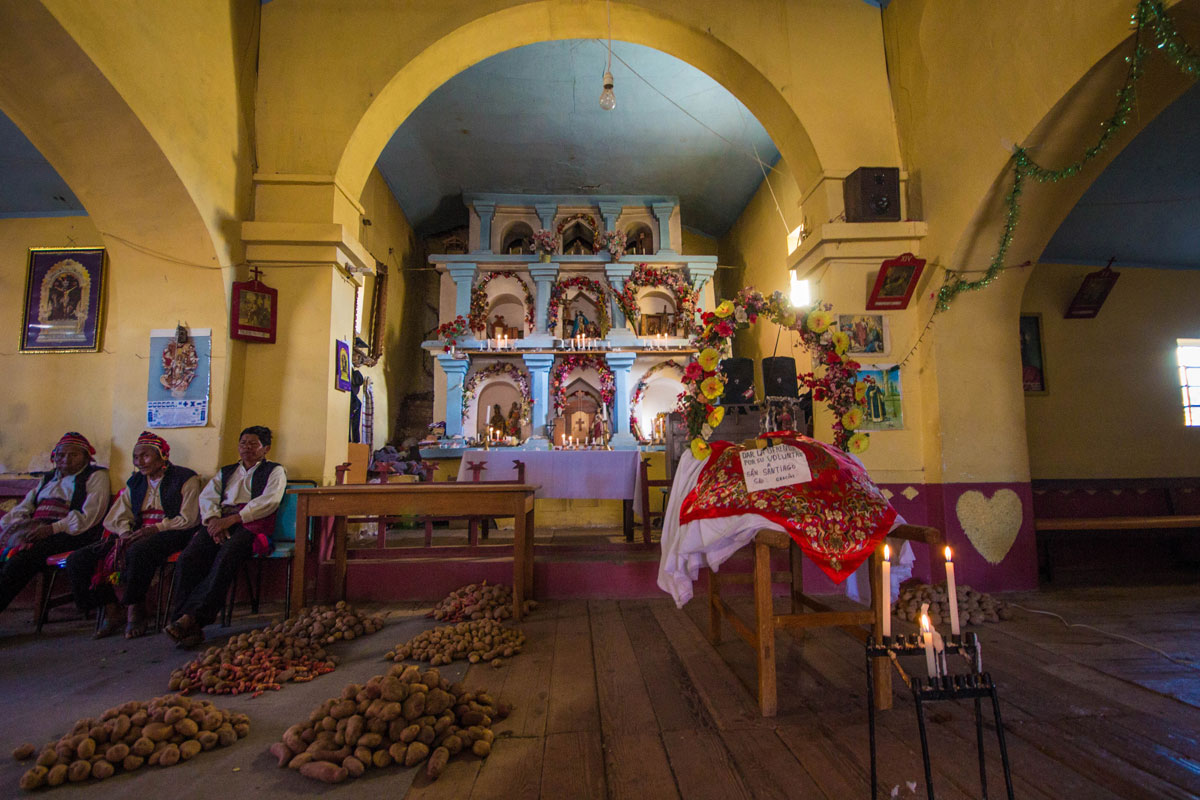 Elder Taquileanos sit among potatoes in the Catholic Church on Isla Taquile on Lake Titicaca Peru