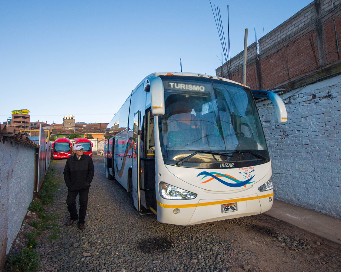An Inca Express Cusco to Puno bus picks up passengers in an alley in Cusco Peru