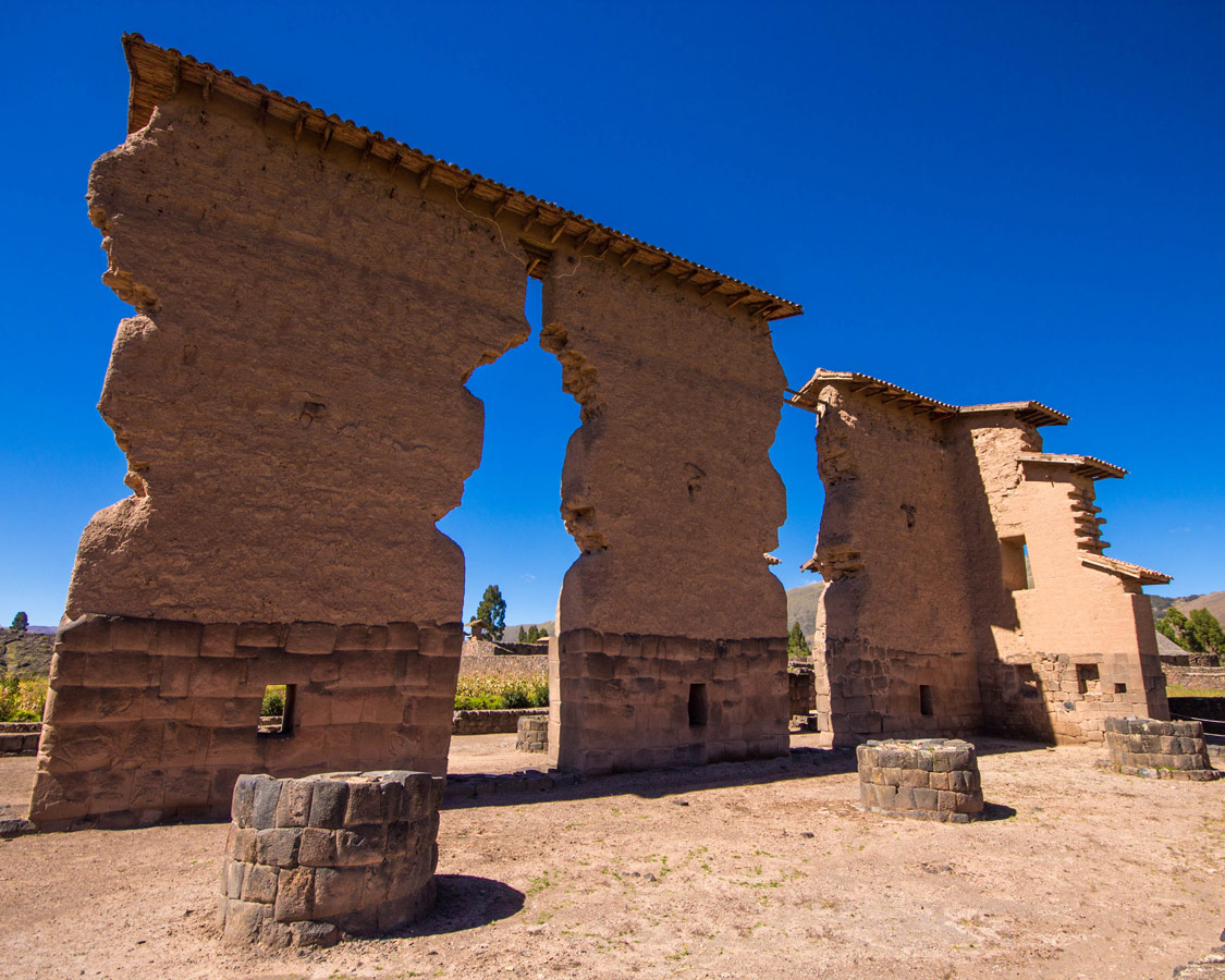 The towering 14 meter high Inca ruins of Raqchi Peru stand out against the blue sky on a stop on the Cusco to Puno bus