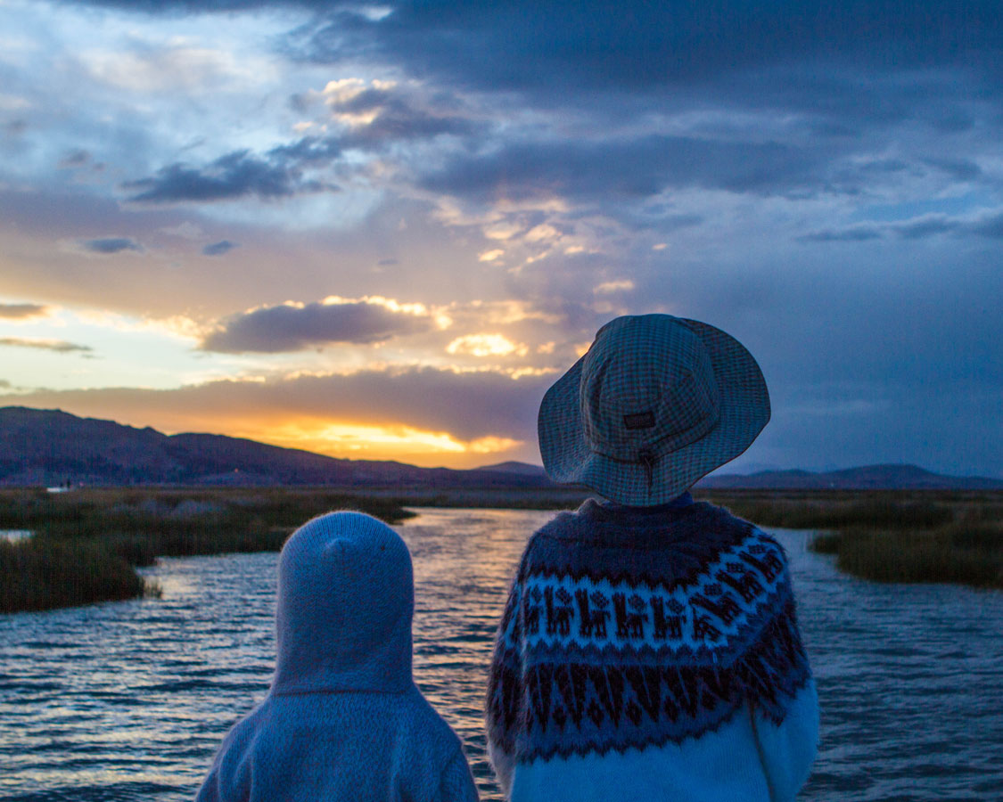 Two boys watching the sunset over lake Titicaca Peru on a journey to Lake Titicaca with kids