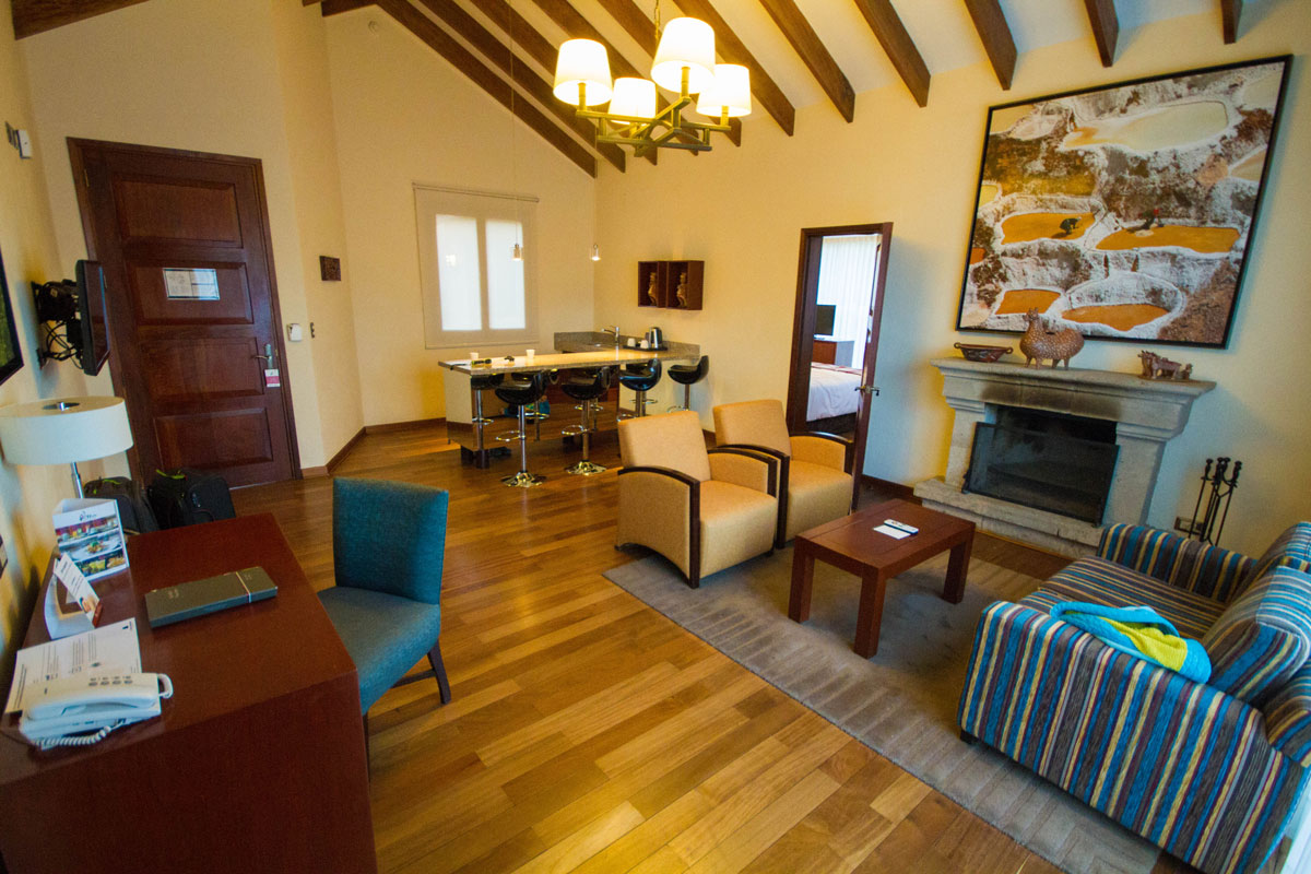 A desk, kitchenette, chairs and and couches sit near a fireplace at the Living room of the Andean Cottage at the Casa Andina Private Collection Sacred Valley Peru