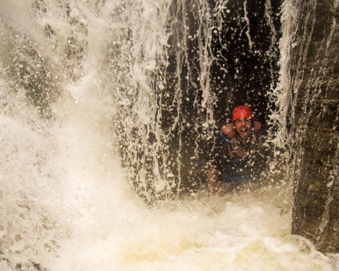 A man in whitewater rafting gear peers out from inside a waterfall at the base of Wolfs Creek in Letchworth State Park in New York State