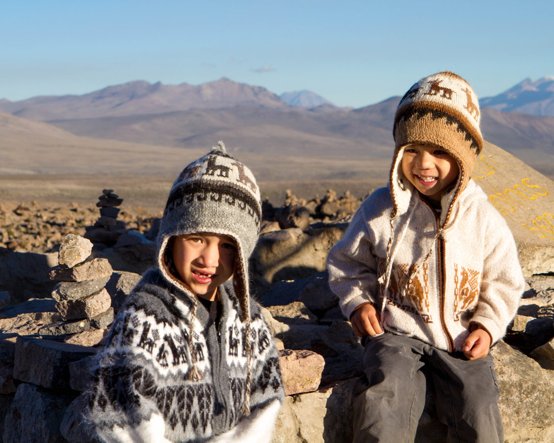 Two young boys wear alpaca hats and sweaters smile among piledrocks at Patapampa Pass in the Andean Mountains on the way to see the Andean Condors in Colca Canyon with kids