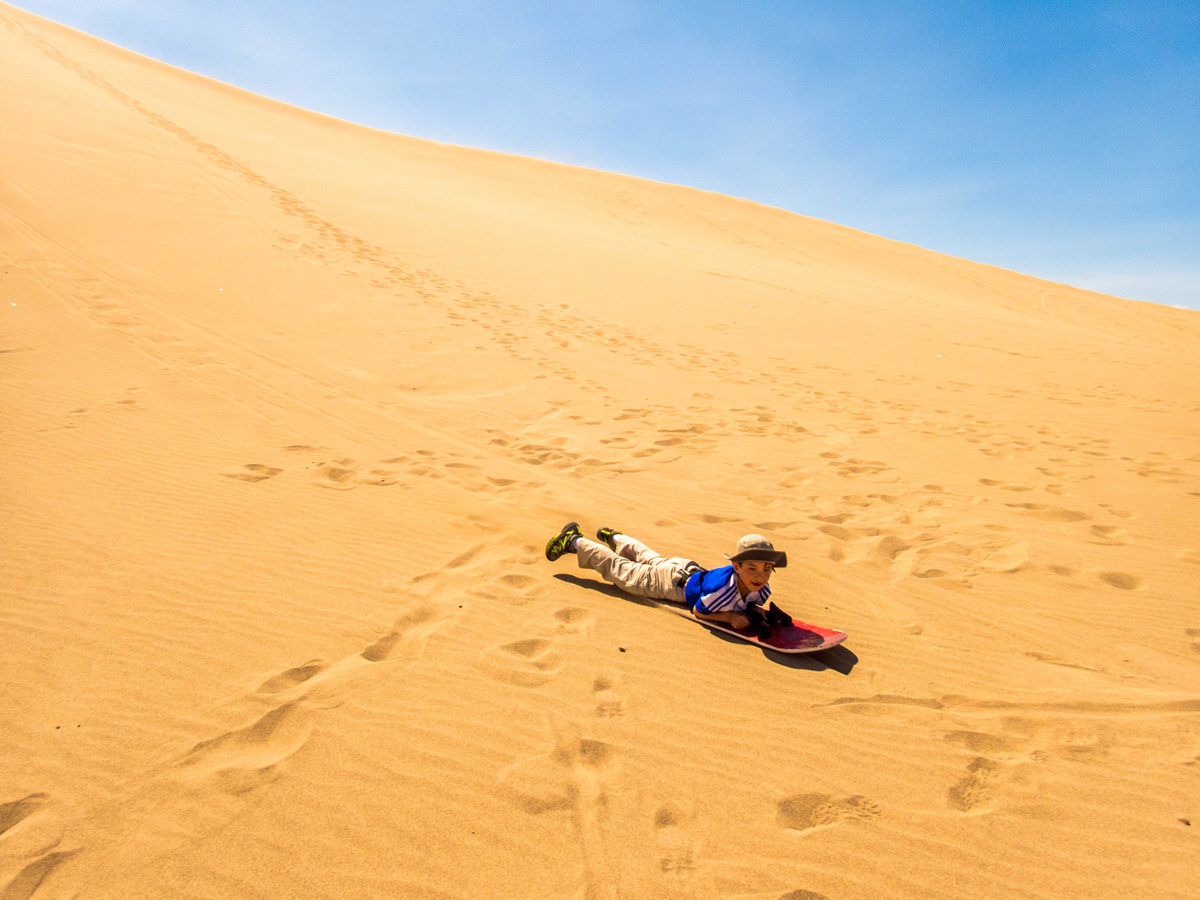 A young boy rides his sandboard down the dunes of Huacachina Peru after exploring Paracas Peru and the Ballestas Islands National Marine Reserve