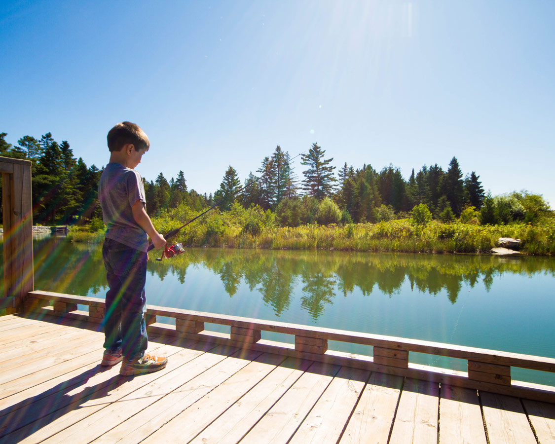 A young boy concentrates while fishing from the boardwalk in Providence Bay Manitoulin Island. Fishing for salmon is one of the top things to do on Manitoulin Island