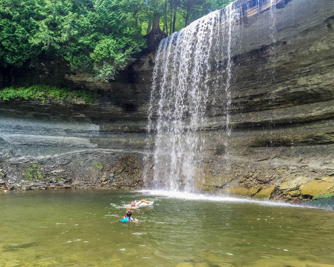 A father and some swim under a waterfall on Manitoulin Island. A swim in Bridal Veil Falls is one of the top things to do on Manitoulin Island