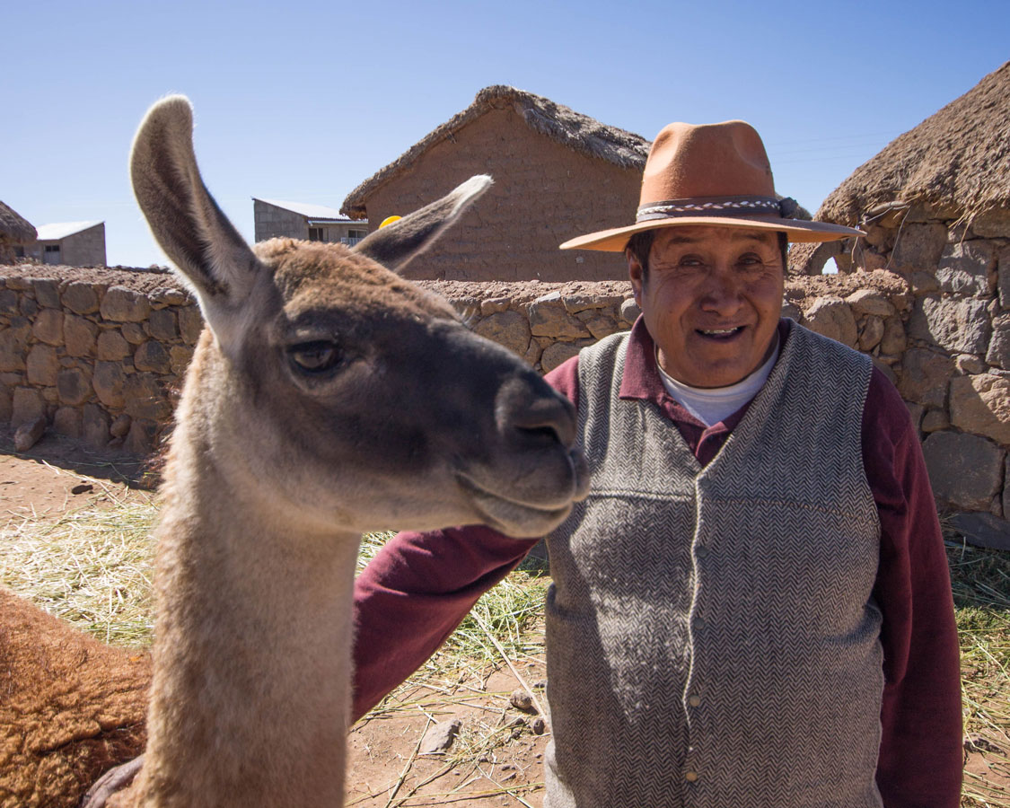 A Peruvian villager stands with a Llama in Peru with kids on a 14 day Peru itinerary