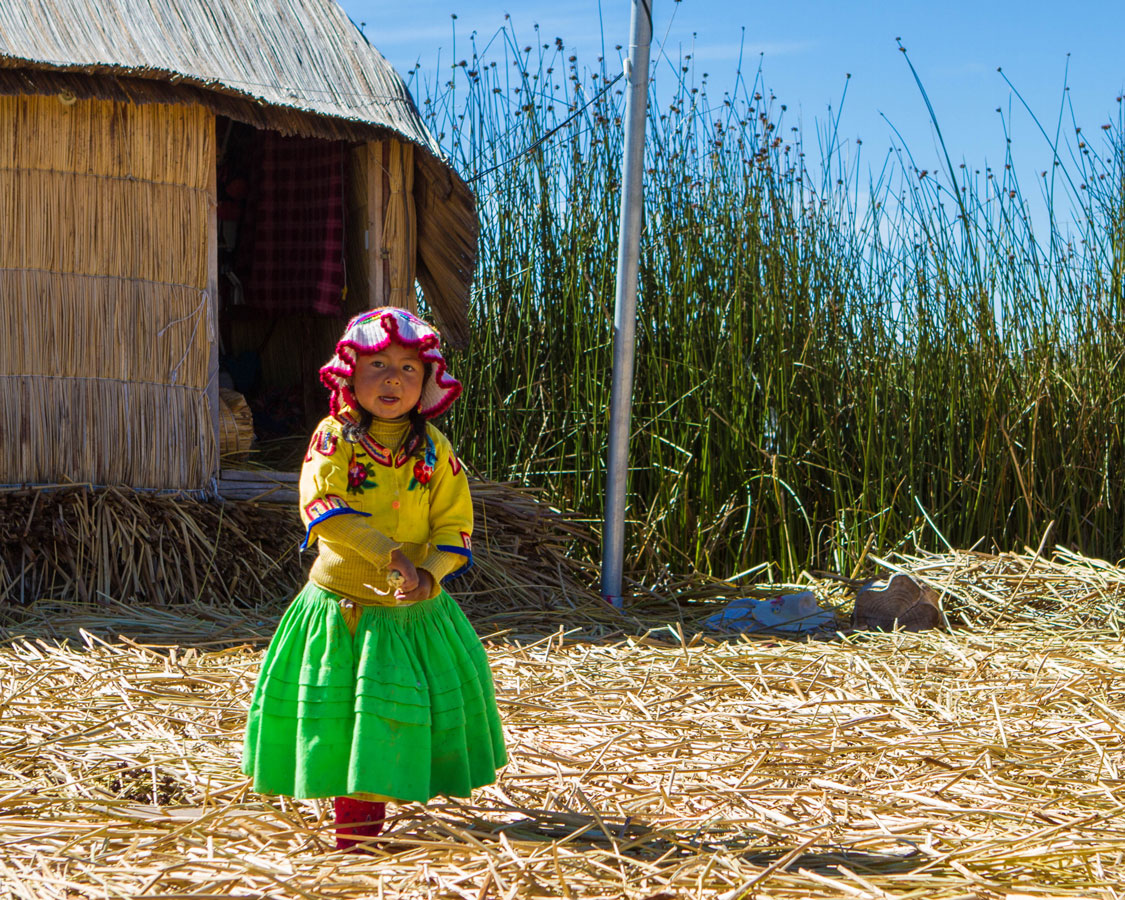 A young Uros girl on Isla de los Uros on Lake Titicaca near Puno Peru with kids on a 14 day Peru itinerary