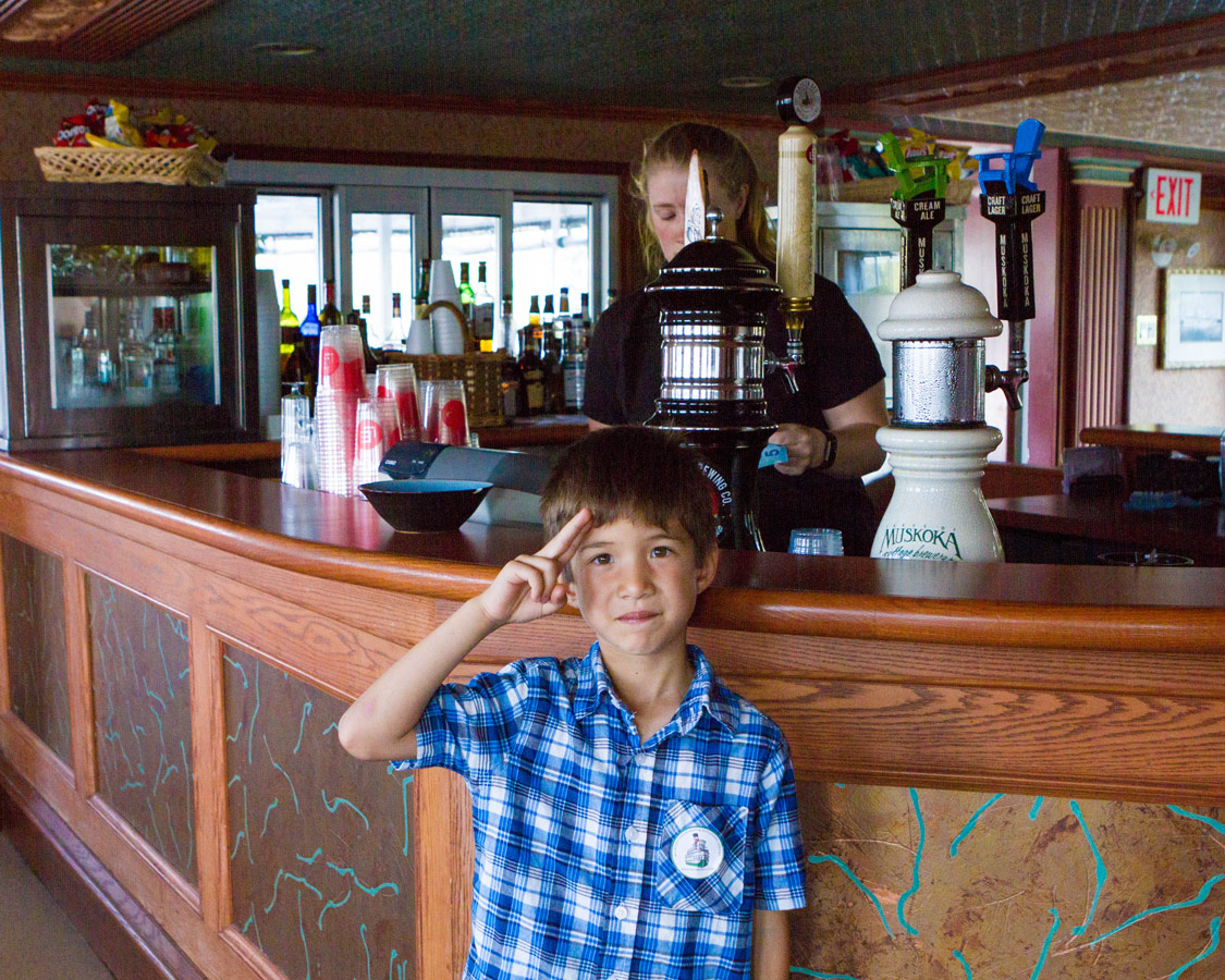A boy gives a salute at the bar on the Muskoka Lake Steamship Wenonah II in Huntsville Ontario