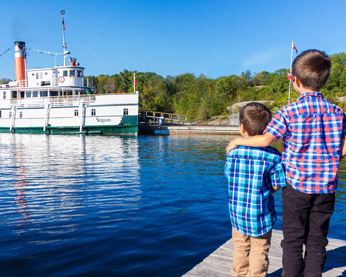 Two boys watch a Lake Muskoka Steamship from a dock in Huntsville Ontario