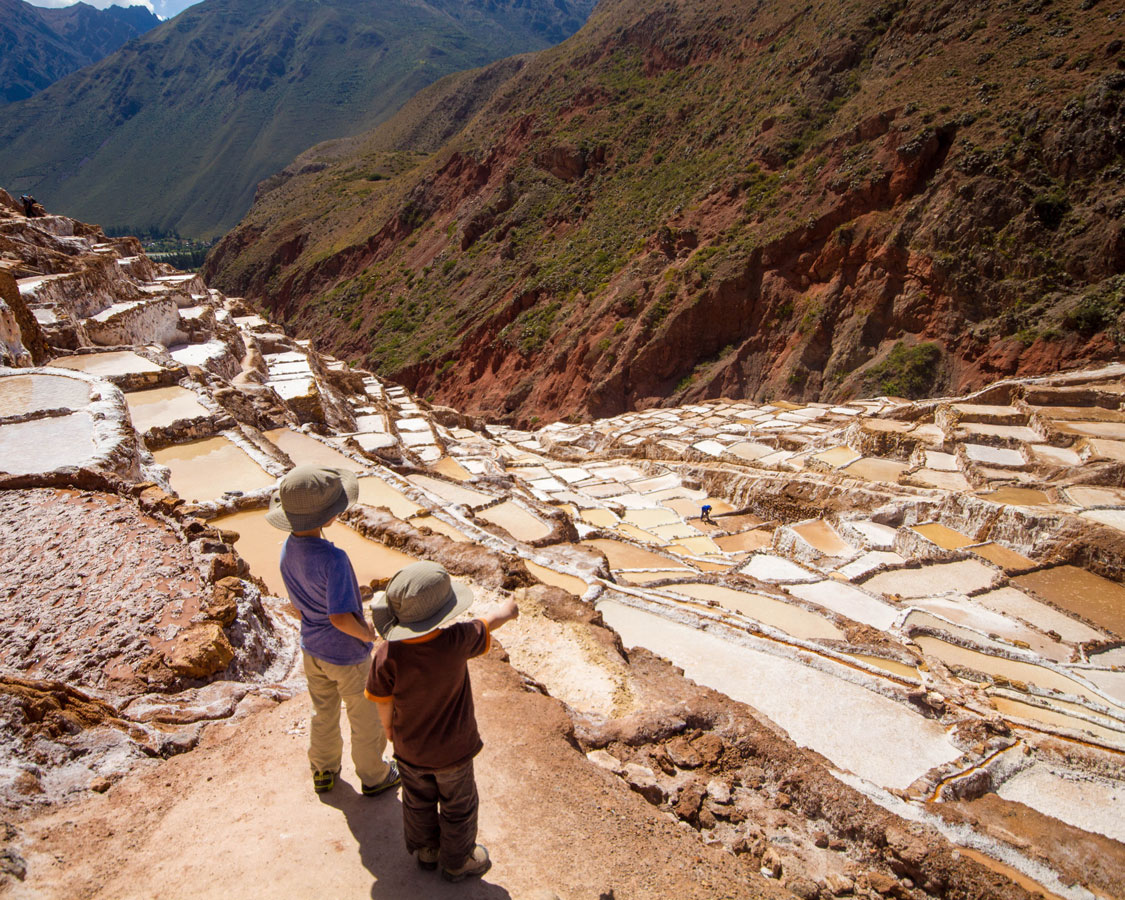 Looking out over the Salt Pans of Maras in the Sacred Valley of Peru with kids