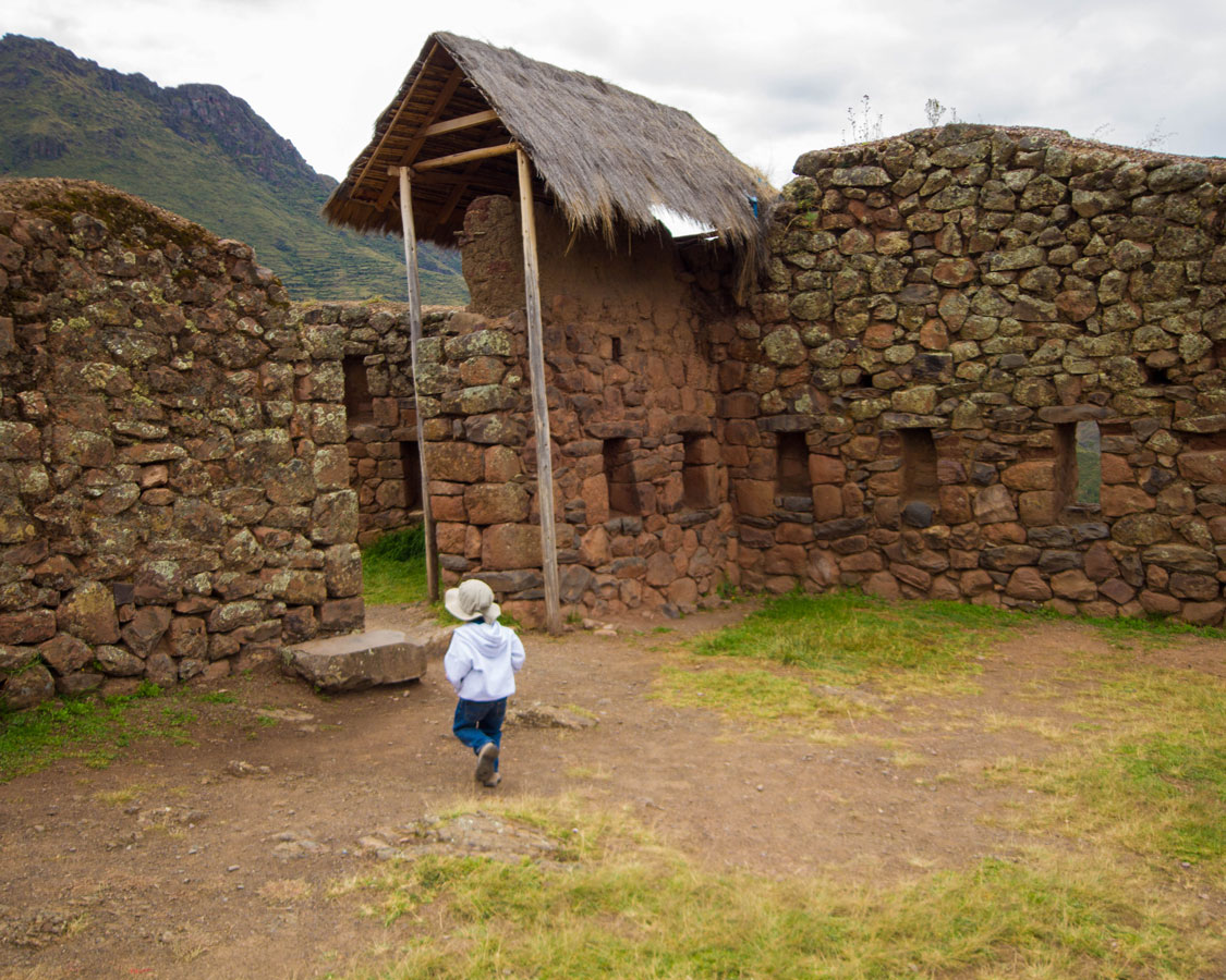 Running through the building of the Pisaq Archaeological Park in Pisac Peru with kids on a 14 day Peru itinerary