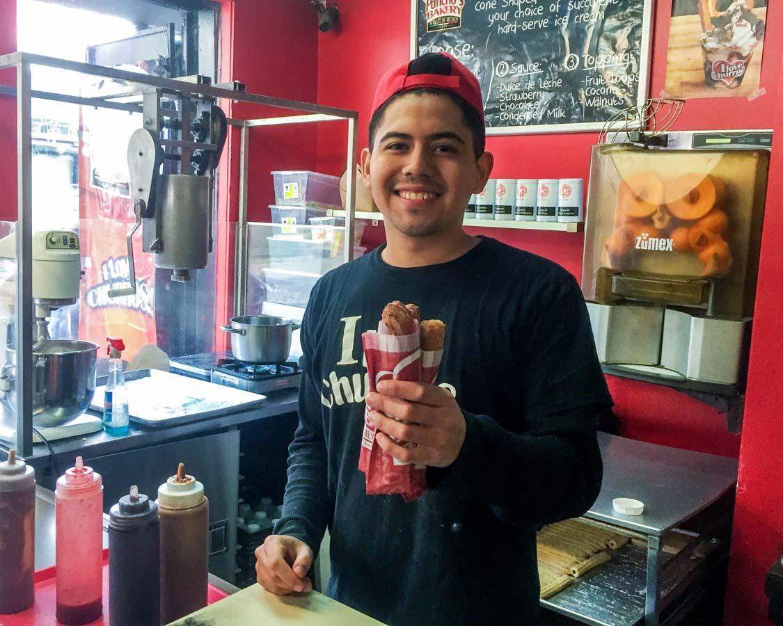 Serving churros at Pancho's Bakery in Kensington Market Toronto Food tour with Tasty Tours Toronto