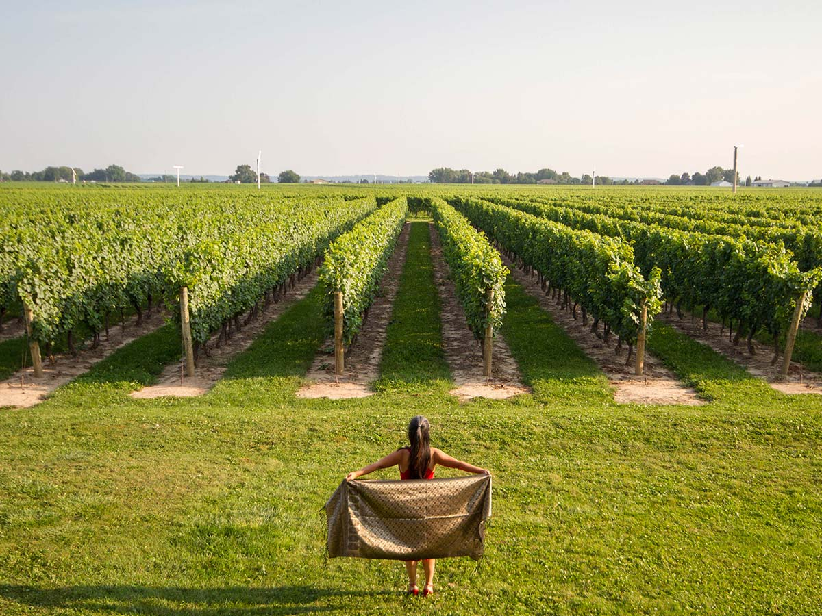 Christina Wagar poses in front of the vineyards in Niagara on the Lake Ontario