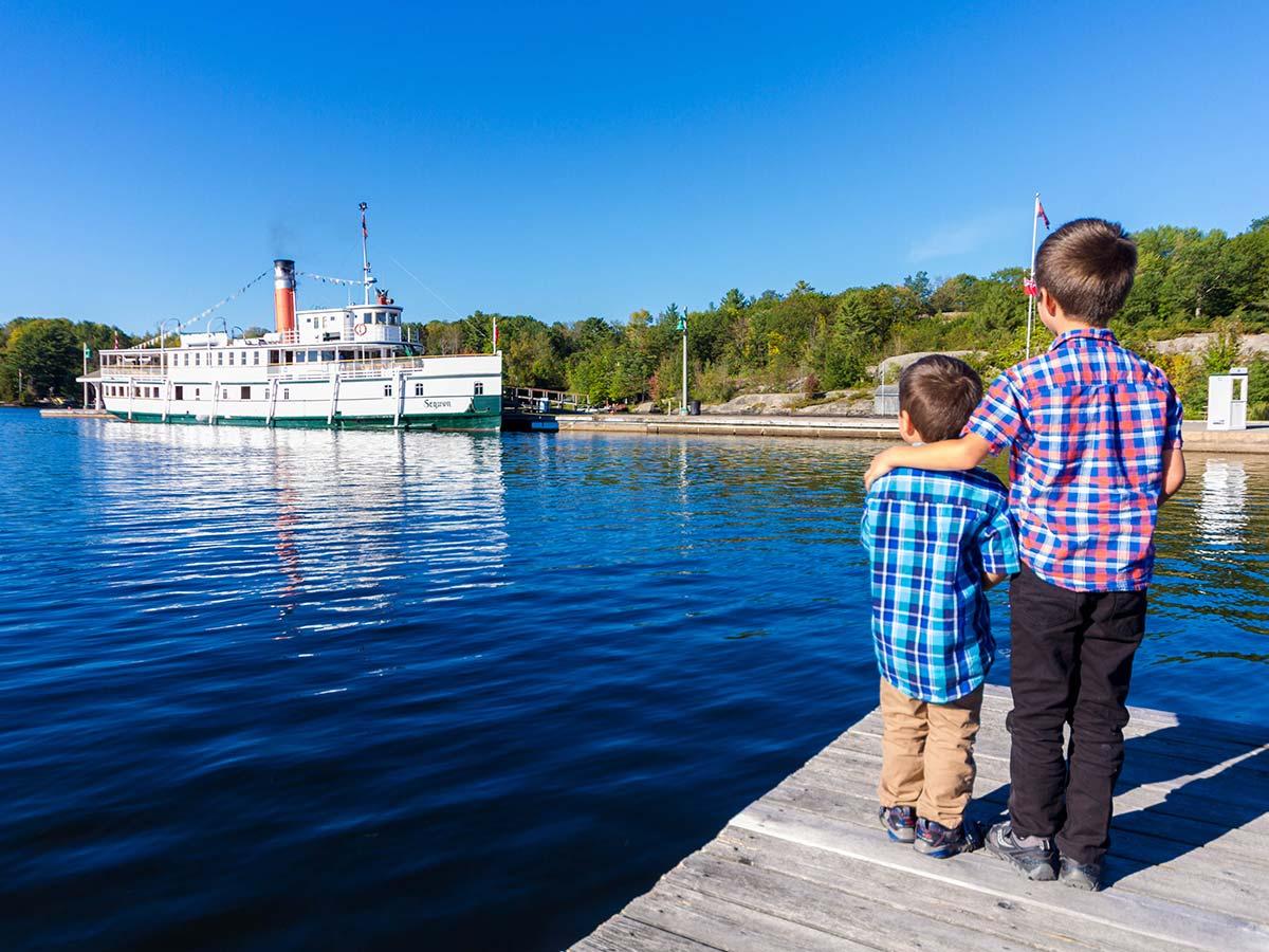 Two boys watch a Lake Muskoka Steamship from a dock in Huntsville Ontario