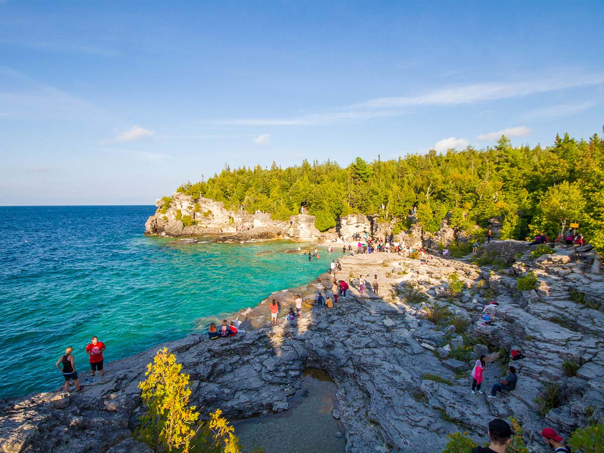 Visitors to Bruce Peninsula National Park lounge on the rocks near the Grotto