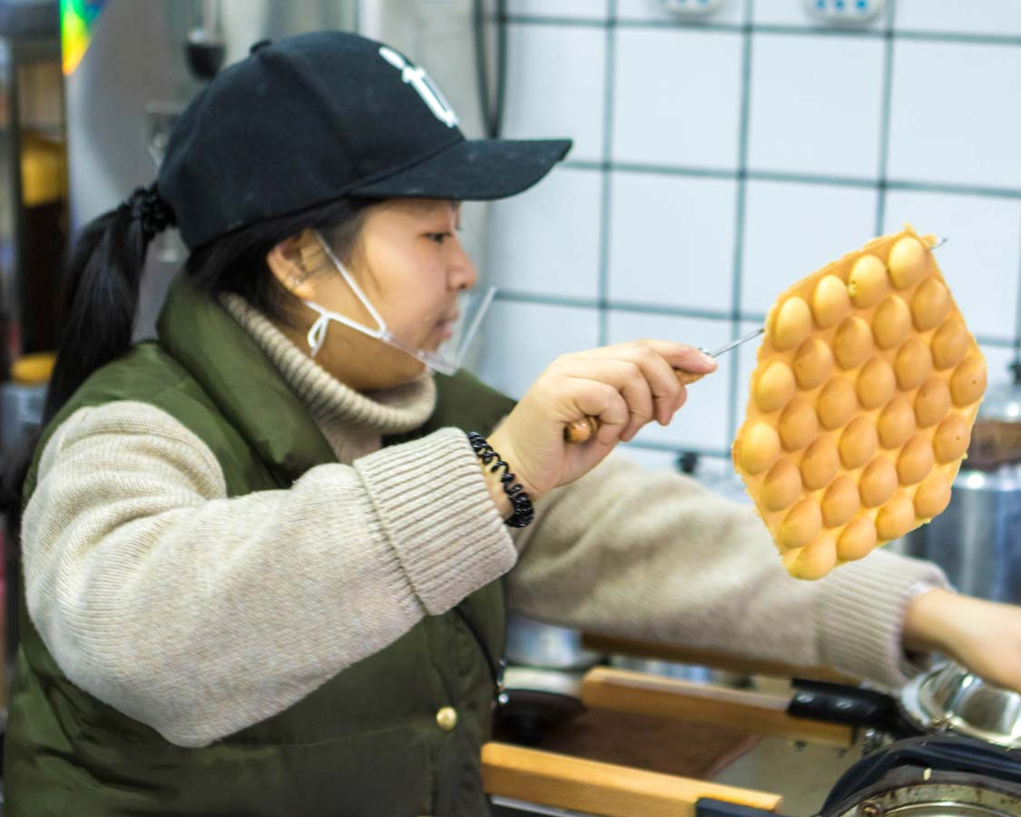 A shopkeeper at Law Kong Yuen Milk Tea Shop makes Shanghai-style waffles on a food tour