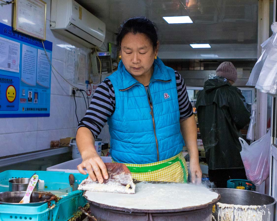 A streetside food vendor prepares wraps at a concession during a Shanghai food tour