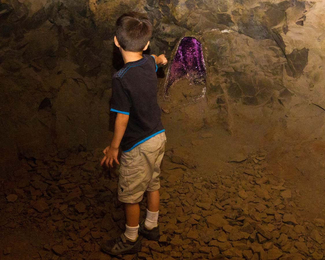 A young boy points at a purple geode in Wanda Mines near San Ignacio Argentina