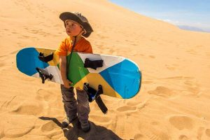 About Us child traveler D Wagar sandboarding in Huacachina Peru