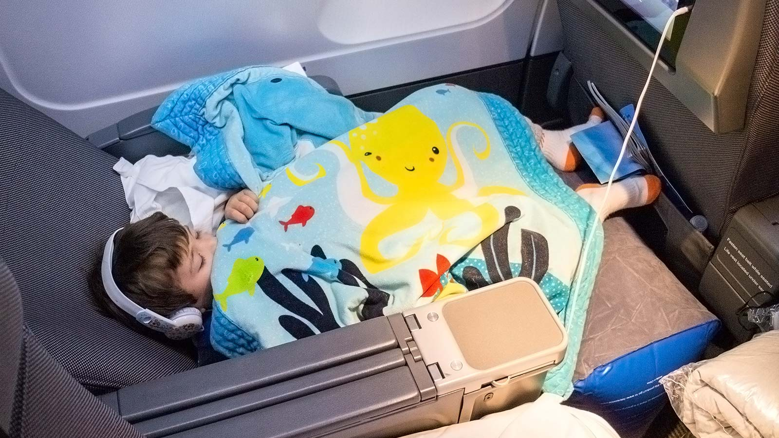 The 1st Class Kid Travel Pillow is an inflatable footrest for airplanes that fits in the space between seats in order to create a seamless reclining area for children to fly legs up. There are things that users need to know about flying with an airplane leg rest and we lay out everything we learned from our experience.