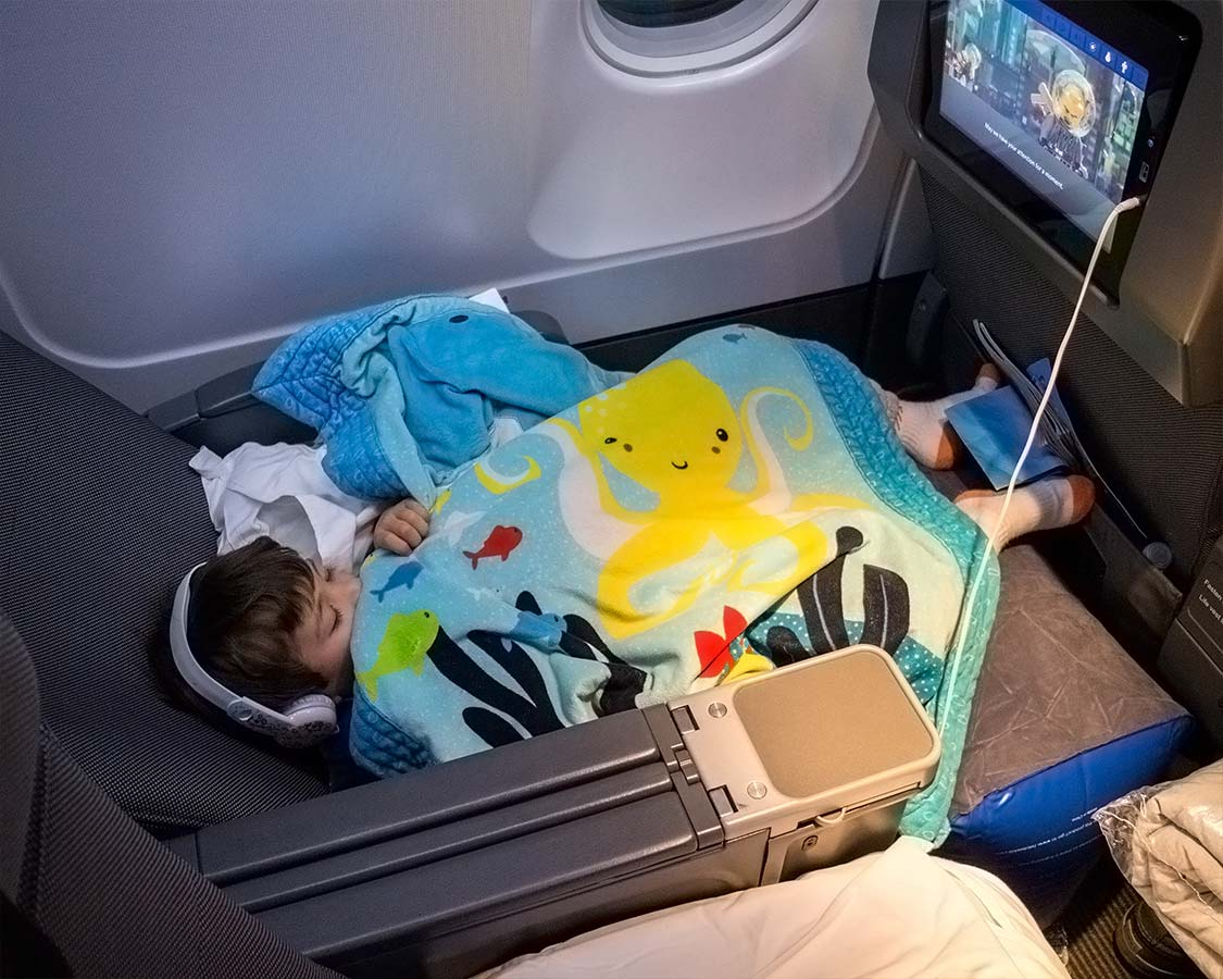 Boy sleeps on an airplane using children's travel pillow