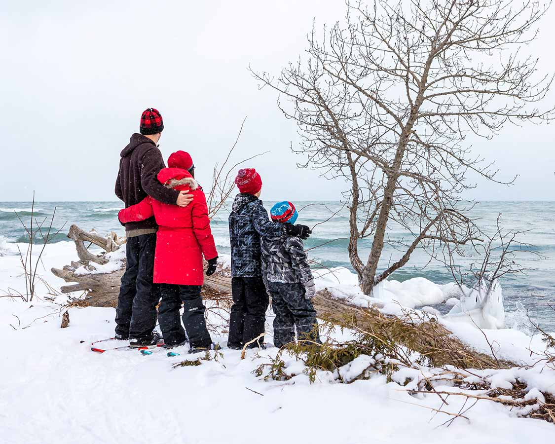 Family snowshoeing in MacGregor Provincial Park in winter