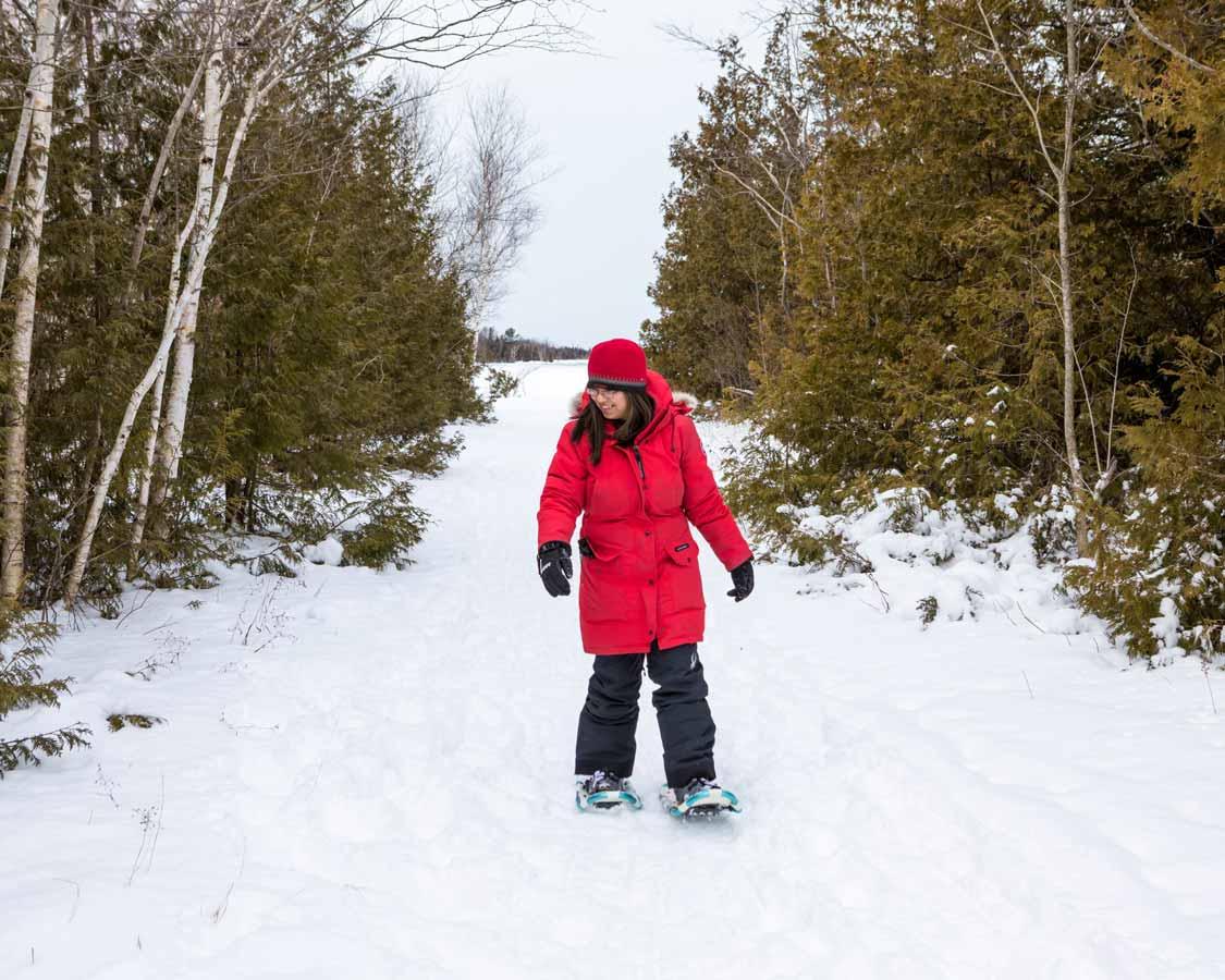 Woman snowshoeing in Macgregor Point in winter
